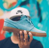 person holding nike sb suede low top sneaker
