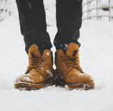 person wearing pair of brown leather work boots stepping on the snow